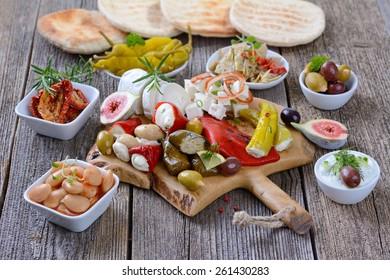 Mixed Greek antipasti on a wooden cutting board