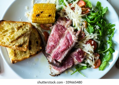 Mixed grill steak with corn and bread