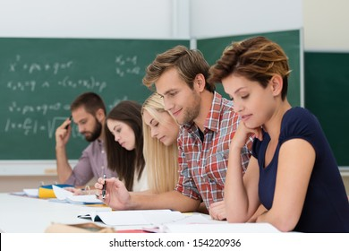 Mixed group of Caucasian determinated students studyng, looking at their notes at their desks in the class, with a chalkboard in the background