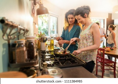 Mixed group of friends having fun while cooking a meal in a warm and welcoming kitchen. Two women takes care of the pots on the stove , while the sun comes in through the window