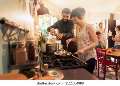 Mixed group of friends having fun while cooking a meal in a warm and welcoming kitchen. a couple takes care of the pots on the stove , while the sun comes in through the window