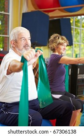Mixed group in gym exercising with latex band
