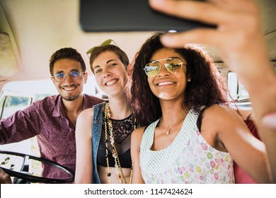 Mixed group of happy young people in a camper van having fun using a smartphone. They look hipster and going vacation