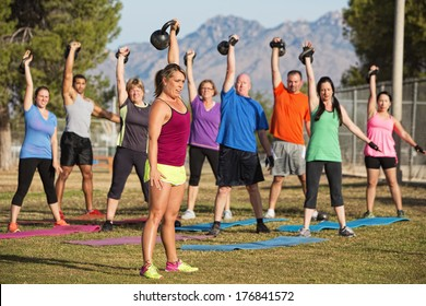 Mixed group of men and women lifting weights outdoors