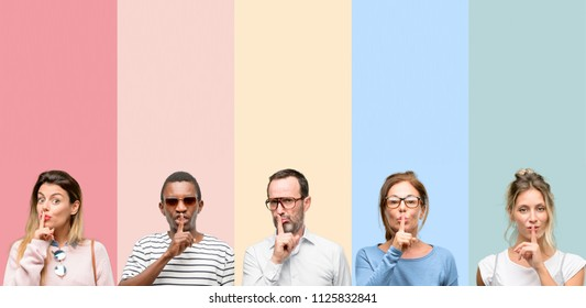 Mixed group of people, women and men with index finger on lips, ask to be quiet. Silence and secret concept
