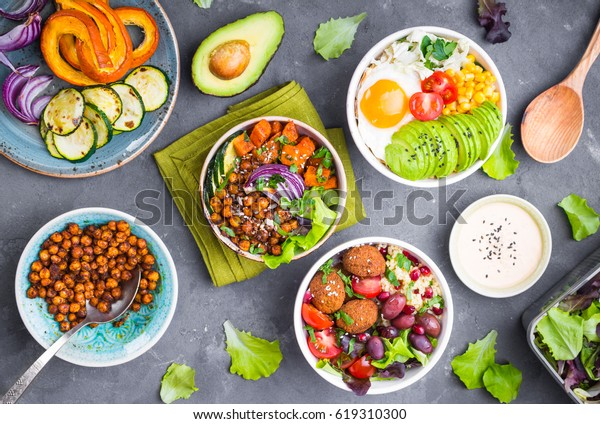 Mixed healthy vegetarian buddha bowl salads with vegetables, sweet potato, falafel, bulgur, avocado, eggs