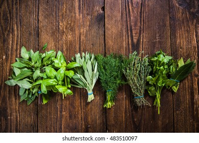mixed herbs lay on wooden table from above