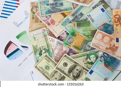 Mixed international paper money and financial graphs background