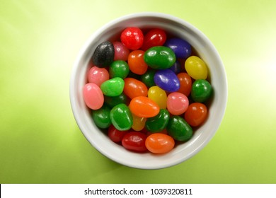 Mixed up jelly beans with mid tones.  A white bowl with just the right amount for a snack.