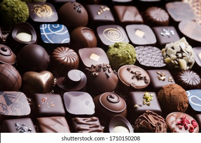 Mixed luxury dark and milk chocolate truffles. Assorted delicious handmade chocolate pralines in a row. Full frame background. Studio shot. Close-up.