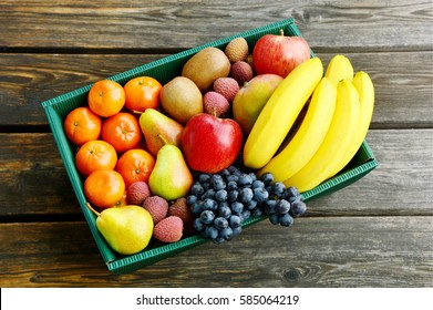 Mixed many type of winter fruits in the paper box for a gift or for transport on wooden background.