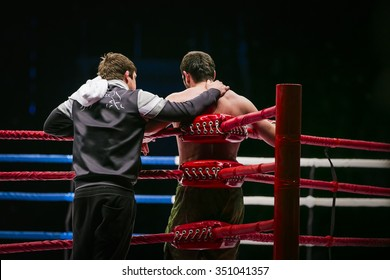 mixed martial arts fighter (MMA) stands in corner ring next to him coach. break between rounds in fight