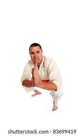 a mixed martial arts master shows off his deadly moves. isolated on white with room for your text. shot with a Fisheye lens for fun effects and Selective Focus. Focus on his face