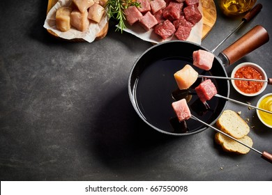 Mixed meat fondue with pork or veal and beef viewed from above with fresh herbs, seasoning and dips on a dark grey granite with copy space