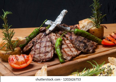 mixed meat grill on wooden platter wit rosemar, tomato and green pepper. Meat ball, chops and steak meat. Black copy space.