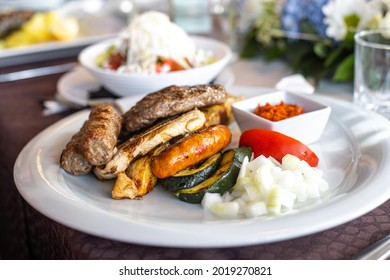 Mixed meat plate with cevapcici, grilled pork, sausage, and onions. Traditional Balkan dish. Delicious barbecue cuisine.