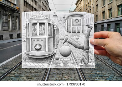 Mixed media image showing a hand-held piece of paper with a pencil drawing depicting tramways with a man upside down head in floor and bubbles flying with a street and buildings in the background.