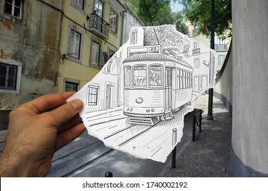Mixed media image showing a hand-held piece of paper with a pencil drawing depicting a tramway in city with apartments in the photo background.