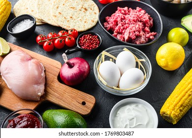 Mixed mexican food background, raw organic ingredients for tacos with chicken and beef meat, corn tortilla, salsa, chilli over black background, side view.