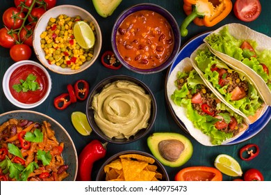 Mixed mexican food. Party food. Guacamole, nachos, fajita, meat tacos, salsa, peppers, tomatoes on a wooden table. Top view. Tex-mex cuisine. Assorted appetizers. Cuisine of Mexico