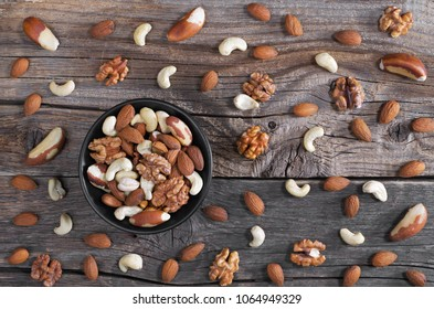 Mixed nuts in black bowl and scattered on old wooden background, top view. Healthy food