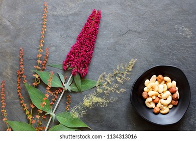Mixed nuts in bowl with fresh flowers and grasses on slate background - flat lay