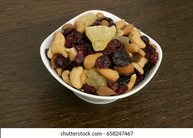 Mixed nuts in a bowl on wood grain table