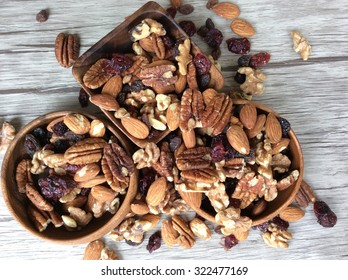 Mixed nuts with cranberries and raisins in three wooden bowls spilling over