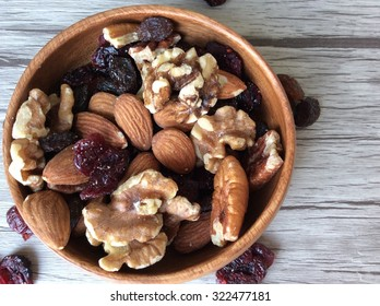 Mixed nuts with cranberries and raisins in a wooden bowl