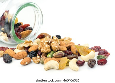 Mixed nuts and dried fruits spilt from bottle isolated on white background