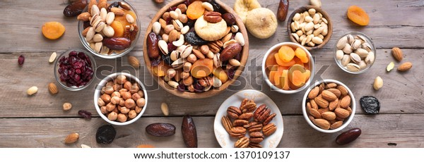Mixed nuts and dried fruits in wooden bowl on wooden background, top view, banner. Healthy snack - mix of organic nuts and dry fruits.