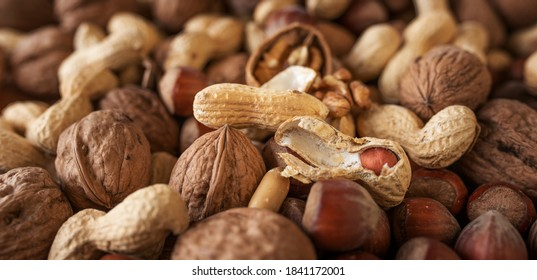 Mixed nuts. Healthy snack with walnuts, peanuts, hazelnuts. Horizontal background with short depth of field for a nutrion concept. Space for your text.