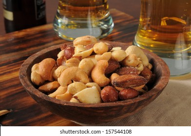 Mixed nuts on a bar counter with tall glasses of beer