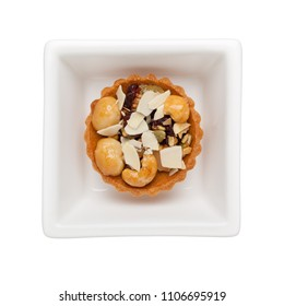 Mixed nuts tart in a square bowl isolated on white background