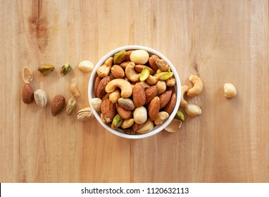mixed nuts in white ceramic bowl on wooden background