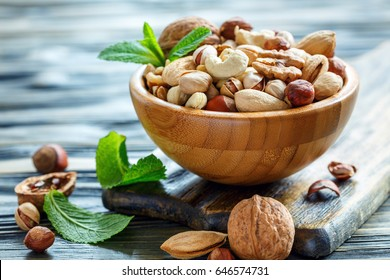 Mixed nuts in a wooden bowl on old table, selective focus.