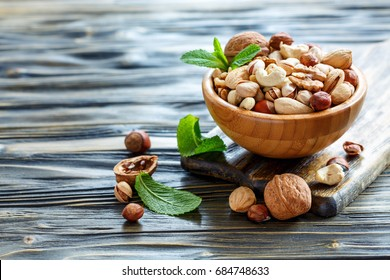 Mixed of nuts with a wooden bowl on old table, selective focus.