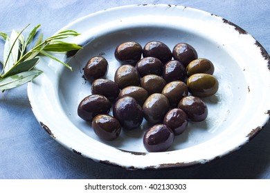 Mixed olives in a antique enamel plate with olive leaves