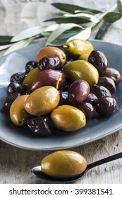 Mixed olives on a plate with a spoon an olive leaves