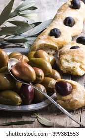 mixed Olives on a plate with a spoon and Bread