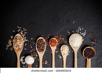 Mixed organic raw rice in wooden spoon over black desk background, with copy space for your text by Top View