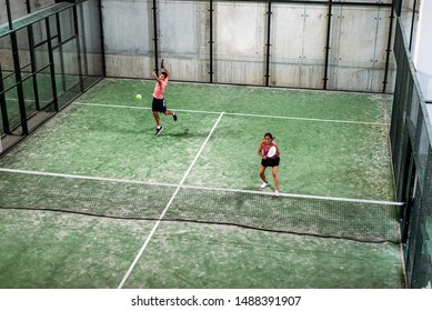 mixed padel match in a green grass padel court indoor behind the net