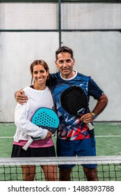 mixed padel players looking at camera and embracing after win a padel match in a green grass padel court indoor