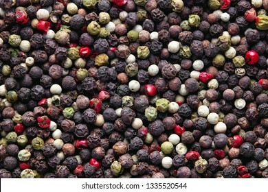 Mixed peppercorns background. Different colored peppercorns, close up.
