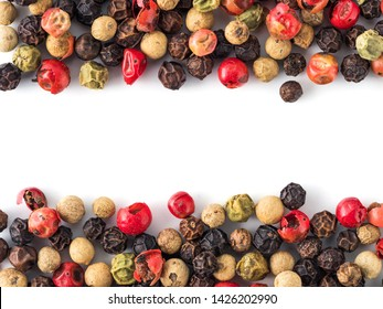 Mixed peppercorns background with white copy space in center. Food background with peppercorns. Different colored peppercorns pattern on white background, top view or flat lay