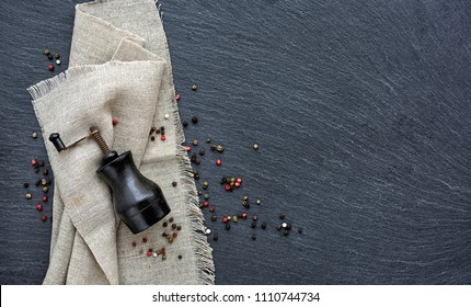 Mixed peppercorns and vintage mill on a slate board, top view