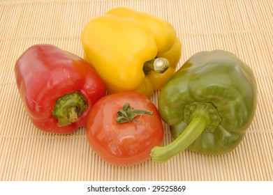 Mixed peppers (capsicums) and tomato on a bamboo table mat