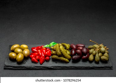 Mixed Pickles on serving board. Olives, Capers and peppers