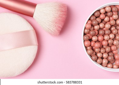 Mixed pink and tan colored glow face pearls blush, brush and puff on pink background. Top view point.