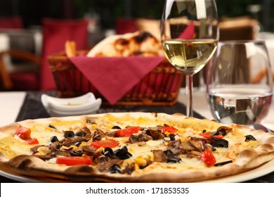 Mixed pizza in a luxury restaurant with wine